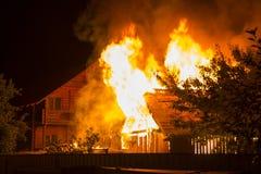 Brennendes Holzhaus nachts Leuchtorangeflammen und dichte Inspektion stockbild