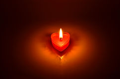 Brennendes rotes Kerzenherz Stockfotografie