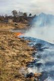 Brennendes trockenes Gras auf der Flussbank Frühling Nahe dem Dorf Stockfoto