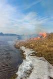Brennendes trockenes Gras auf der Flussbank Frühling Schnee und Feuer Stockfoto