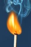 Brennendes Zündholz auf einem blauen Hintergrund. Lizenzfreies Stockbild