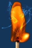 Brennendes Zündholz auf einem blauen Hintergrund Stockbild