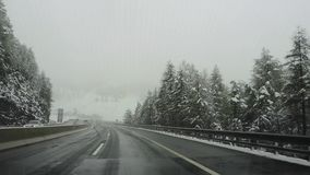 Brennero motorway, Italy. Driving shot, driver point-of-view. Footage driving on highway during a snowfall.  stock footage