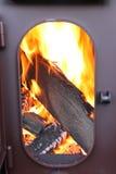 Brennholz brennen in einer Feuerkammer eines Ofens mit einer geöffneten Tür Lizenzfreie Stockbilder
