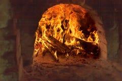 Brennholz, das im alten Ziegelsteinofen brennt Lizenzfreie Stockfotos