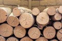 Brennholz gestapelt in einem dekorativen Kamin gegen den Hintergrund von Kunststeinziegelsteinen stockbild