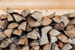 Brennholz gestapelt in einem Woodpile auf hölzernem Hintergrund Stockbild