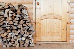 Brennholz gestapelt in einem Woodpile auf hölzernem Hintergrund nahe Holztür Stockbilder