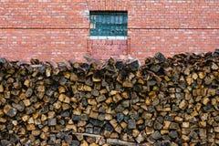 Brennholz gestapelt nahe der Wand des roten Backsteins Stockbilder
