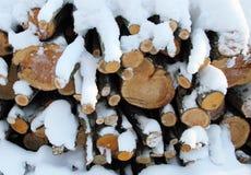 Brennholz im Schnee. Stockfotos