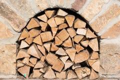 Brennholz wird unter einem Ziegelsteinofen gespeichert stockfoto
