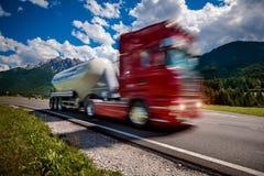 Brennstoff-LKW hetzt hinunter die Landstraße im Hintergrund die Alpen T Stockfotografie