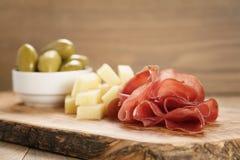 Bresaola用帕尔马干酪和橄榄在切板 库存图片