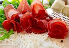 Bresaola with cheese pecorino and arugula Royalty Free Stock Photos