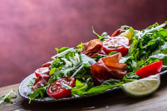 Bresaola de boeuf sec Tomates chaux d'épinards de bébé d'arugula de bresaola de salade et parmesan de fromage Image stock