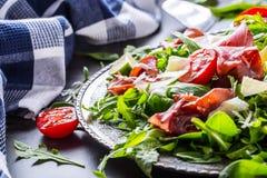 Bresaola de la carne de vaca secada Tomates cal de la espinaca del bebé del arugula del bresaola de la ensalada y parmesano del q Foto de archivo