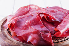 Bresaola over wooden plate Stock Photos