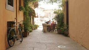 Brescia - Italia: Gente que come en un callejón típico en Italia almacen de video