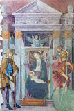 BRESCIA, ITALY, 2016: The fresco of Madonna with the St. Christopher and St. Roch in church Chiesa del Santissimo Corpo di Cristo Royalty Free Stock Photography