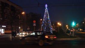 Brest, Białoruś - 13 2015 Grudzień Rozjarzona choinka na ulicie przy nocą Bulwar kosmonauta, ruchliwie ruch drogowy zbiory