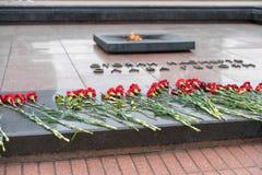 BREST VITRYSSLAND - JULI 28, 2018: Blommor på gravstenen av den okända soldaten och evigt ljus Titeln säger `-härlighet till hjäl royaltyfri foto