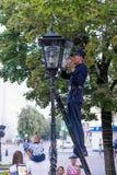Bresta, Bielorrússia - 30 de julho de 2018: O Lamplighter ilumina uma luz de rua manualmente fotos de stock royalty free