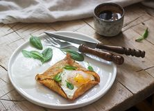 Breton buckwheat crepes with egg, spinach and cream, filed with the coffee. Rustic style stock image