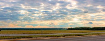 Brett fält med gräs och färgrik molnig himmel på solnedgången Royaltyfri Bild