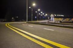 Brett modernt slätt tomt exponerat med huvudvägen för asfalt för gatalampor med den ljusa vita markera teckenlinjen på natten Has royaltyfri bild