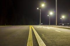 Brett modernt slätt tomt exponerat med huvudvägen för asfalt för gatalampor med den ljusa vita markera teckenlinjen på natten Has fotografering för bildbyråer