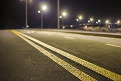 Brett modernt slätt tomt exponerat med huvudvägen för asfalt för gatalampor med den ljusa vita markera teckenlinjen på natten Has royaltyfri fotografi