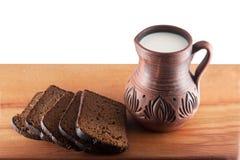 Brett och kannan av mjölka på trätabellen royaltyfri fotografi