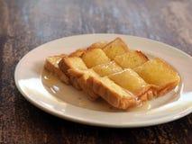 Brett smör på rostat bröd med sötat förtätat mjölkar Arkivbilder