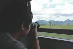 Brett vinkelskott av den unga asiatiska turisten som tar ett foto av det sceniska naturberget med den yrkesmässiga kameran i drev Arkivfoto