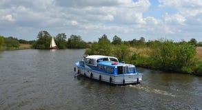 Bretter Kreuzer und Yacht unter dem Segel, das den Fluss Bure nahe Horning, das Norfolk Broads navigiert stockfotografie