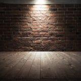 Bretterboden- und Backsteinwand mit Scheinwerferlicht Lizenzfreie Stockfotografie
