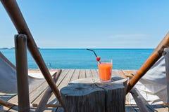 Bretterboden- und Seeansicht mit Liegen und Cocktail Lizenzfreies Stockfoto
