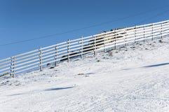 Bretterzaun auf dem Schnee Stockbild