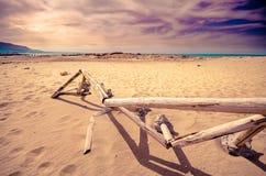 Bretterzaun auf einem sandigen Strand mit bewölktem und buntem Himmel Stockfotos