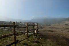 Bretterzaun eingewickelt im Nebel Stockfotos