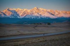 Bretterzaun im Schnee bedeckte Berge Stockfotografie