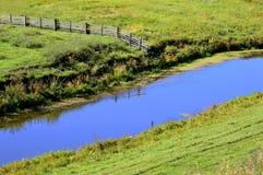 Bretterzaun reflektiert im blauen Fluss Baum auf dem Gebiet Stockbild
