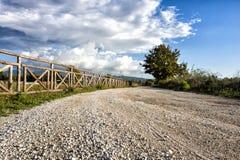 Bretterzaun und alte römische Straße, blauer Himmel mit Wolken Lizenzfreie Stockfotos