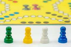 Brettspiel mit unterschiedlichem farbigem Spiel verpfändet auf ihm Ludo oder traurige Brettspielspielzahlen Stockbilder