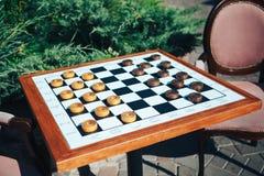 Brettspiele in der Straße auf einem Holztisch und weichen Stühlen Kontrolleur-Spiel stockbild