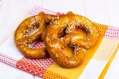 Bretzels bavarois avec les graines de sésame sur les conseils blancs Images stock
