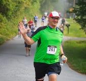 BREVARD, NC 28-ое мая 2016 - счастливый человек бежит в белой гонке белки с над 350 бегунами в Brevard, NC 2016 Спонсируют гонку Стоковое Изображение RF