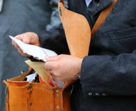 brevbärare med den gamla påsen, medan leverera post Royaltyfria Foton