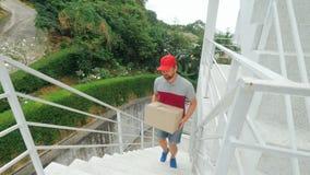 Brevbäraren i likformig klättrar snabbt trappan för att leverera jordlotten arkivfilmer