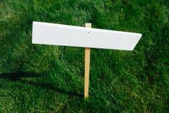 Breve erba sistemata con il segno vuoto bianco fotografia stock
